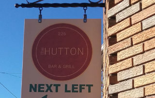 "Sign for the Hutton bar and grill that says ""next left"""