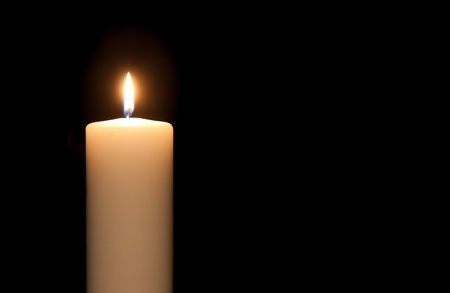 Single candle against dark background