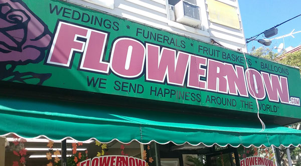 "FlowerNow shop sign has a great tagline: ""We send happiness around the world."""