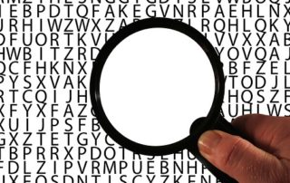 Against a background of letters, the area within a magnifying glass is blank.