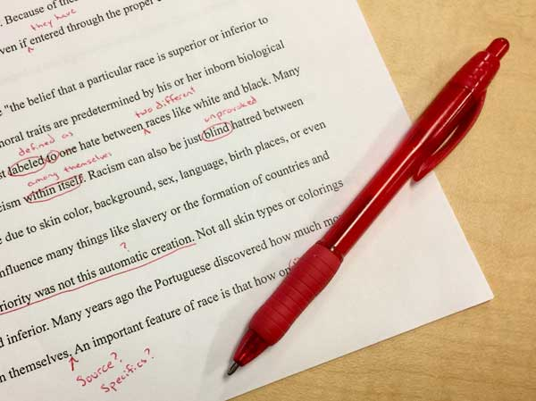 editing grammar on paper with a red pen