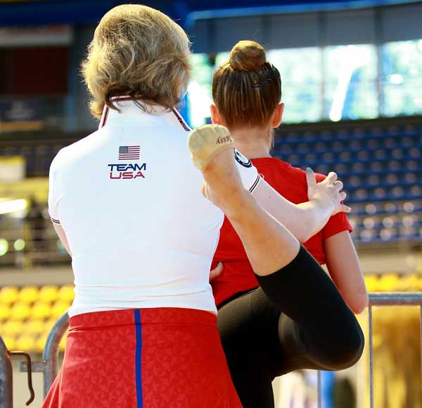Photo of female coach helping young gymnast